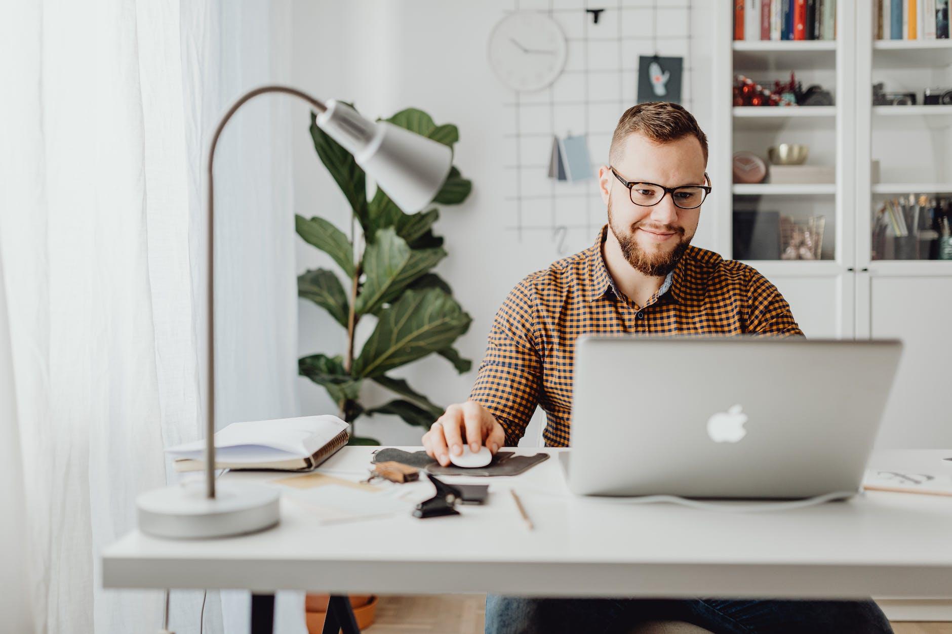 Man smiling at laptop in white office