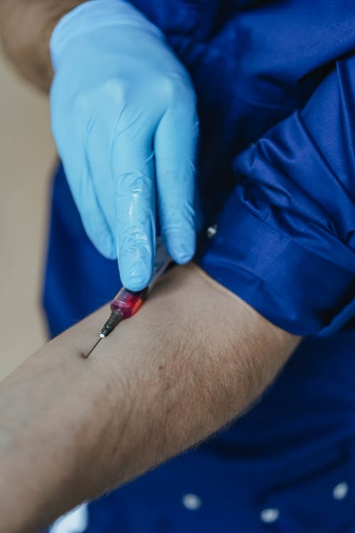 A Person Injecting a Loaded Syringe