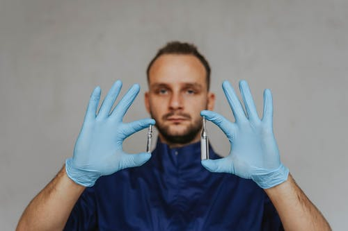 A Doctor Holding Glass Ampoules