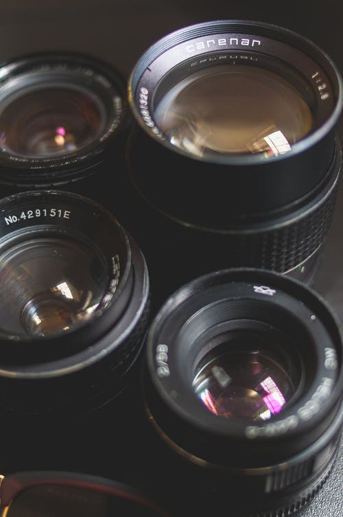 Collection of modern lenses for professional photo camera placed on black surface in photo studio