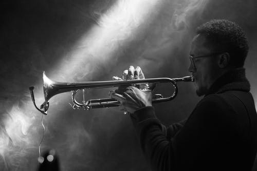 Grayscale Photo of Person Playing Trumpet