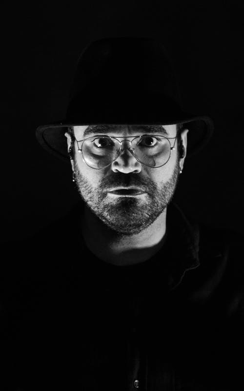 Unemotional adult man in hat and eyeglasses in studio