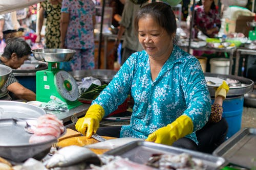 Woman in Blue Long Sleeve Shirt Selling Fish