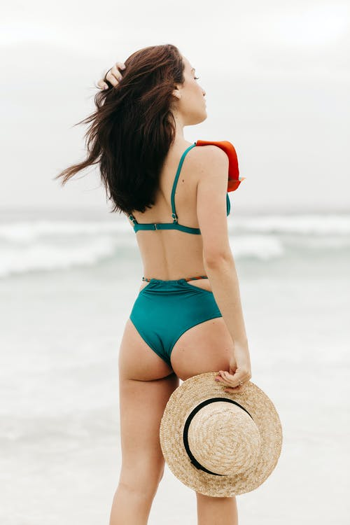 Back view of young dreamy tourist in swimwear with straw hat touching hair and looking away on ocean beach in summer