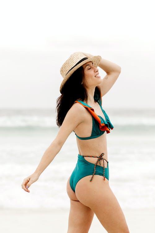 Dreamy tourist in swimwear walking on ocean shore
