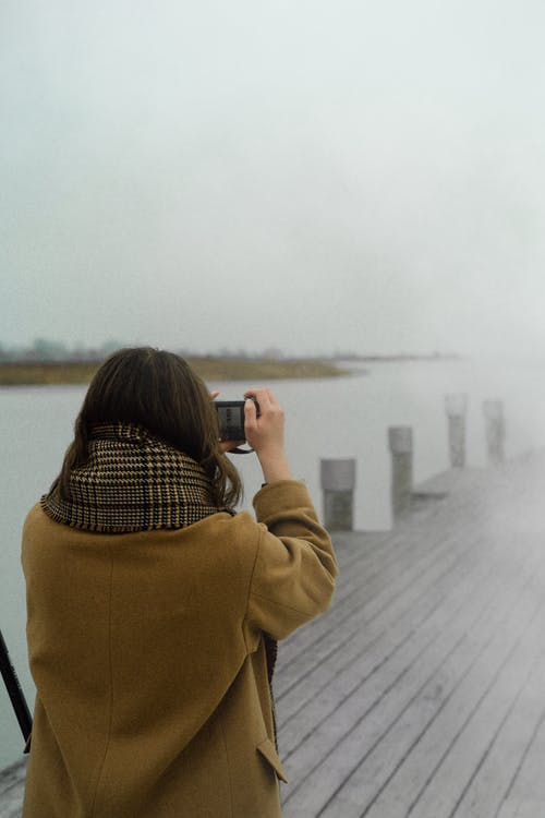 Woman in Coat Taking a Picture Using Her Camera