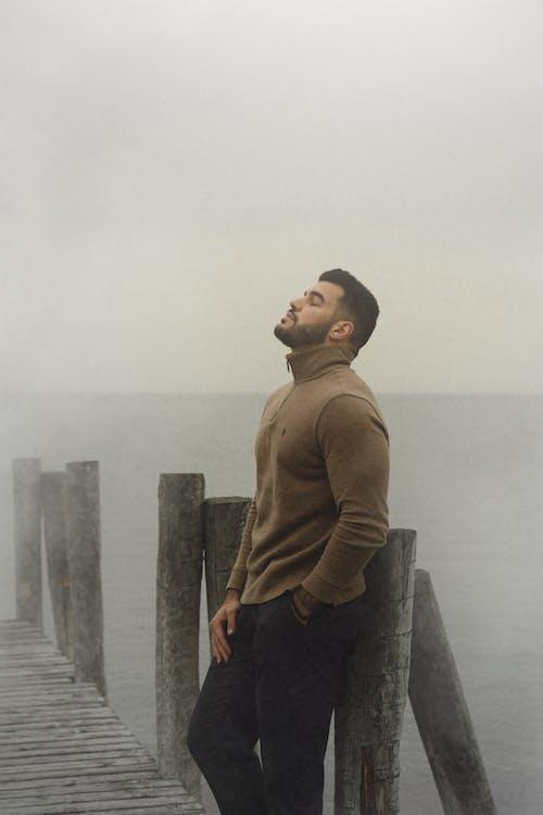 Man in Brown Hoodie Standing on Wooden Dock