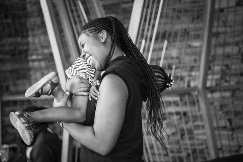 Grayscale Photo of Woman Carrying a Child