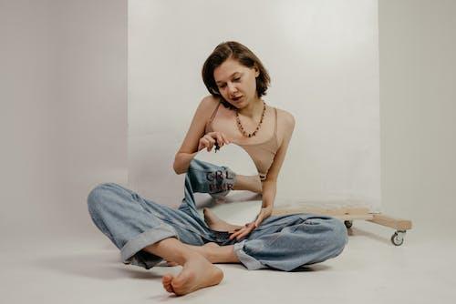 時尚的小姐在地板上休息,並展示與grl Pwr口號的鏡子