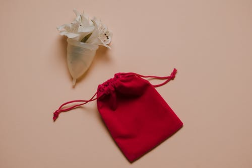Menstrual cup with white gentle flowers placed on pink surface near bag