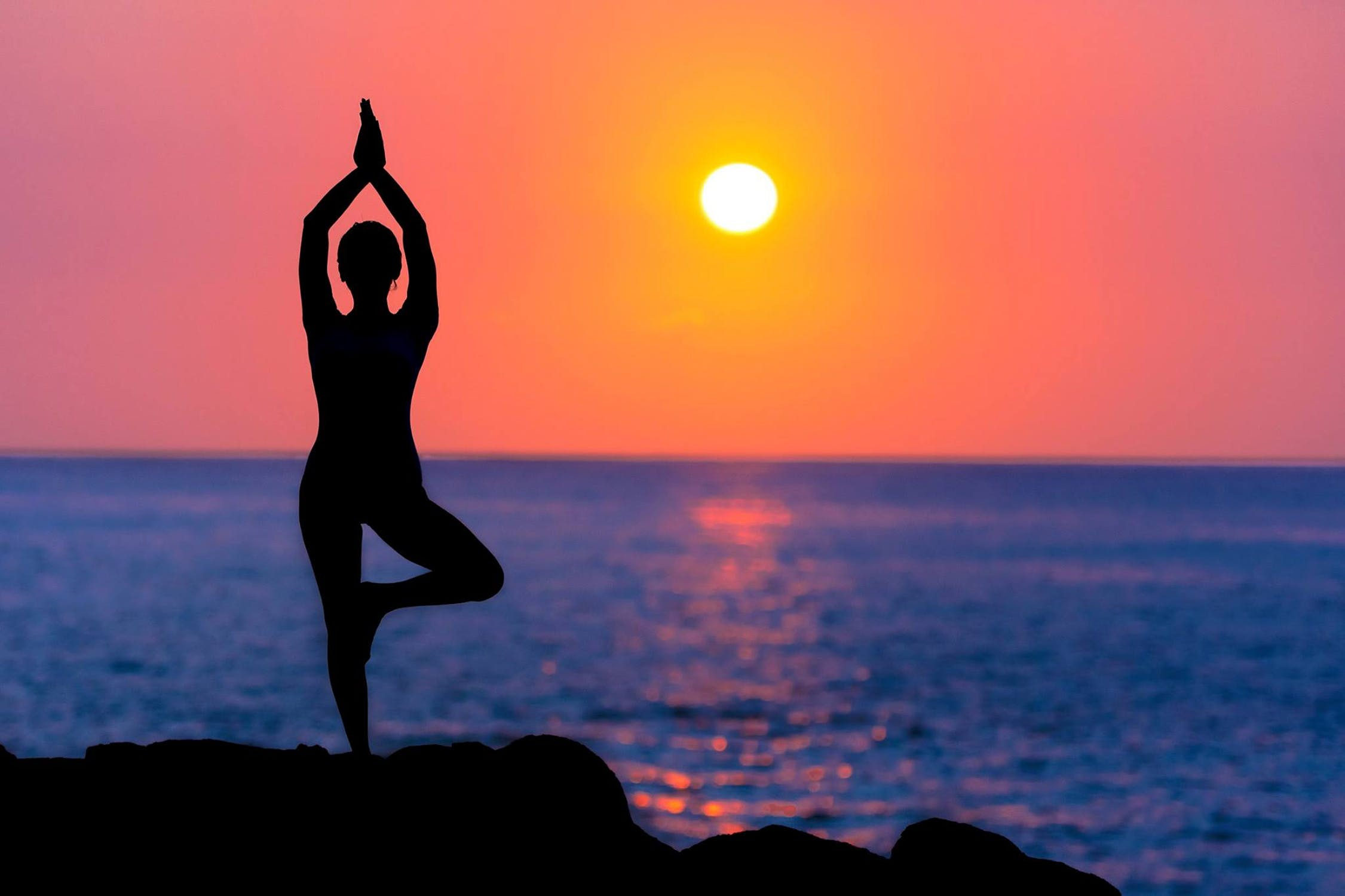 A photo of a CBD user practicing yoga by herself on a serene beach at sunset.