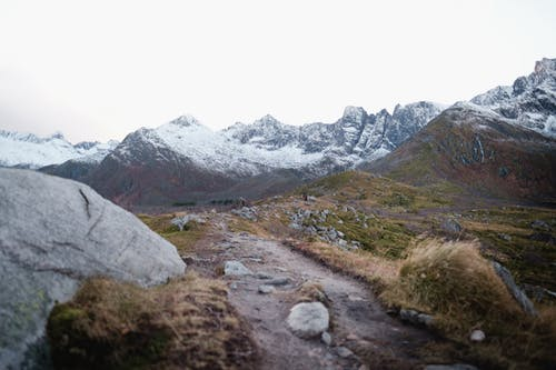 Rough stones on slopes of snowy mountains on cloudy day