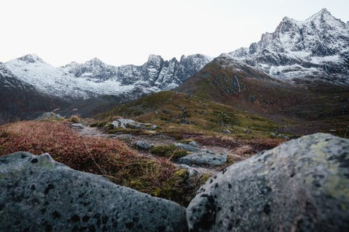 Breathtaking scenery of high snowy mountains placed on rocky terrain in cloudy day