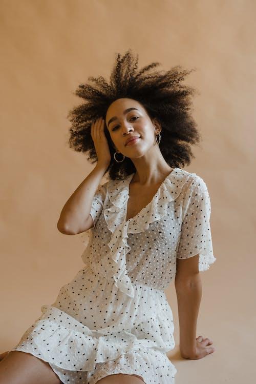 Positive young black woman relaxing in beige studio