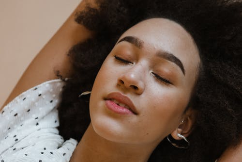 Peaceful young black woman relaxing with closed eyes