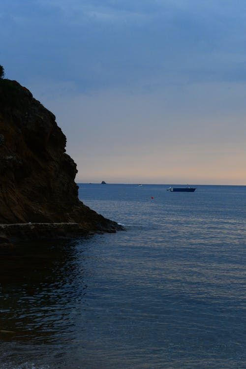 Boat on Sea Near Rock Formation