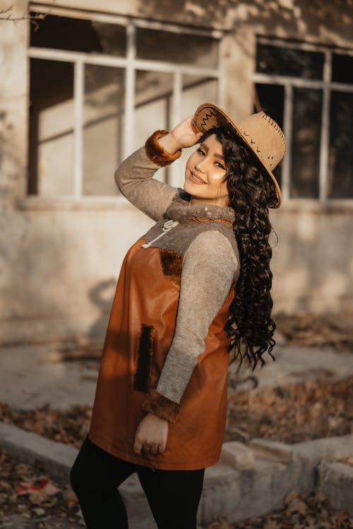 Happy ethnic woman in stylish warm outfit smiling in autumn