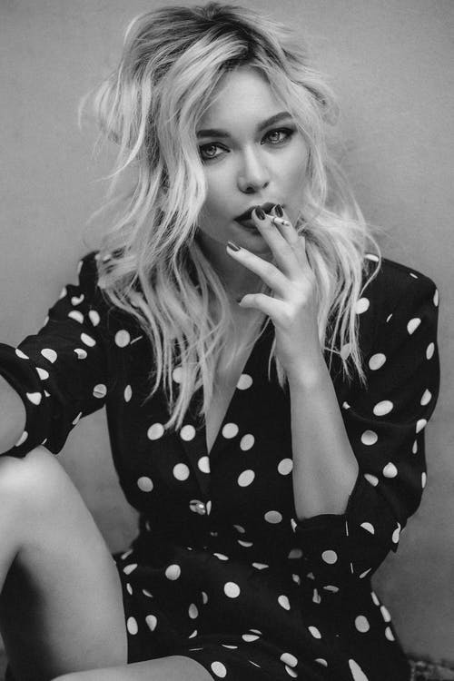 Black and white of confident female in polka dot dress sitting near wall and looking at camera while smoking cigarette on street