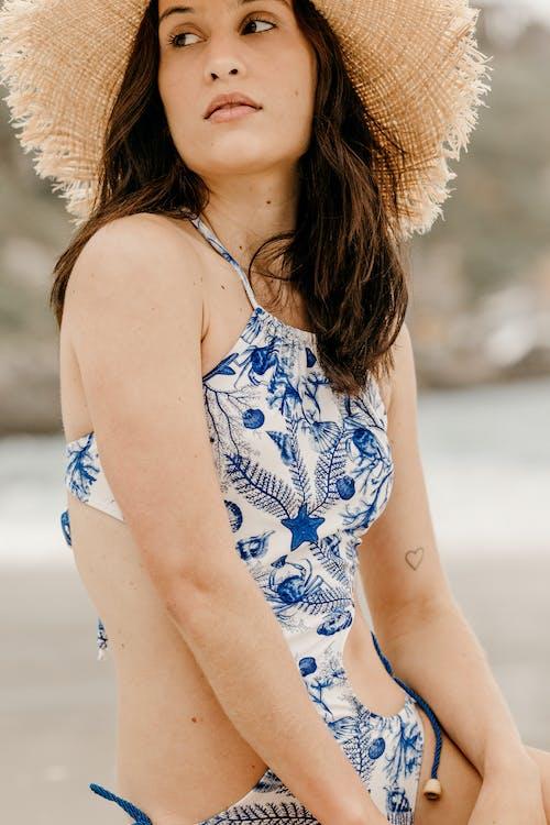 Crop stylish dreamy woman in swimwear on sea shore
