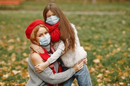 Girl Hugging Woman In Gray Sweater
