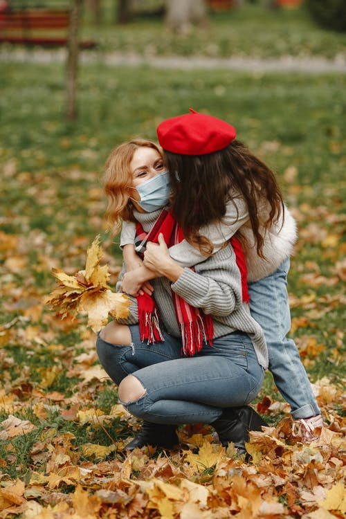 Girl Hugging Woman In Red Hat And Gray Sweater