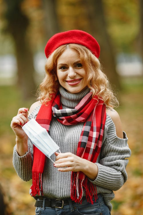 Woman In Gray Sweater And Red Hat Holding A Face Mask