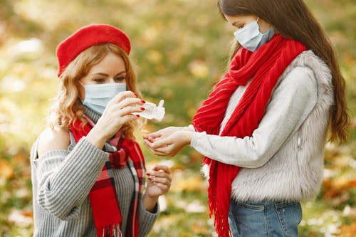 Woman Wearing A Red Scarf And Gray Sweater Holding Hand Sanitizer