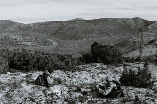 Black and white of full body anonymous male travelers with dog and backpacks resting on ground in highlands