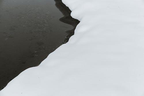 Calm river near snowy bank