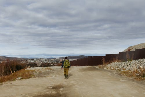 Back view of anonymous male with backpack walking in outskirts of city under cloudy sky
