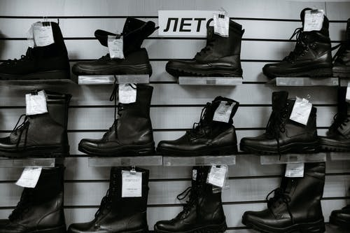 Black and white high leather boots with laces placed on shelves in shop