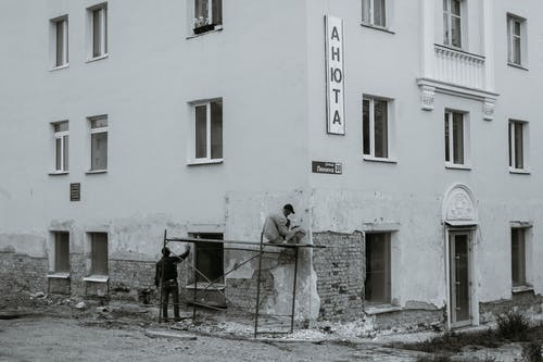 Workers renovating wall of residential house