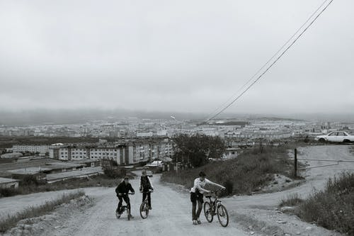 Black and white of anonymous male teenagers riding bicycles on dusty road against overcast sky in city outskirts