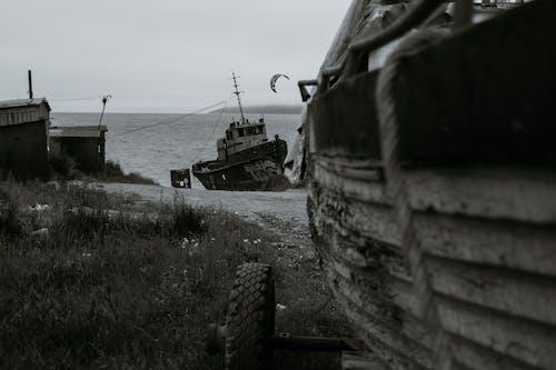 Old boats on seacoast against foggy sky