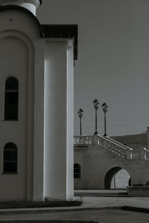 Black and white exterior details of aged Holy Trinity Cathedral with stairway decorated with vintage streetlamps against cloudy sky in Magadan