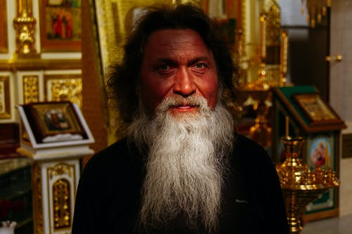 Peaceful senior Orthodox priest with gray beard in cassock standing in church near golden icons and frescoes and looking at camera