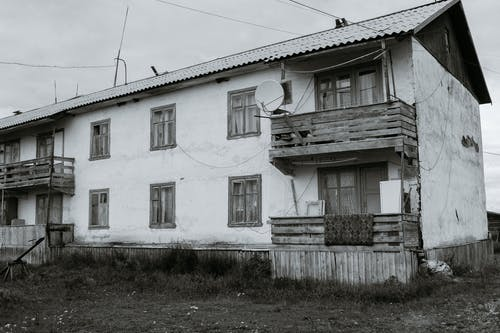 Black and white exterior of old neglected building with wooden balconies and windows located in suburb area under overcast sky