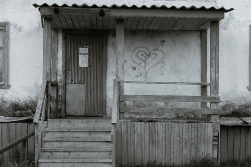 Entrance of aged neglected building with wooden stair and door