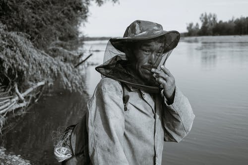 Side view of black and white middle aged Asian male in casual clothes and anti mosquito head net hat standing on lake shore and looking at camera before fishing