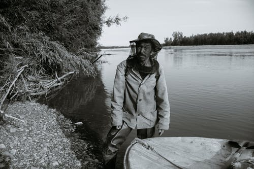 Black and white of calm mature ethnic fisherman in anti mosquito head net hat standing in shallow water of lake near wooden boat and looking at camera
