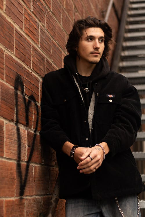 Woman in Black Zip Up Jacket Standing Beside Brick Wall