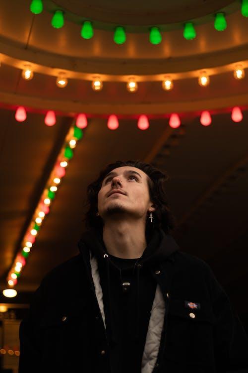 Man in Black Jacket Standing Near Lighted String Lights
