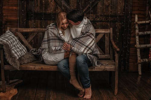 Loving couple hugging on wooden bench at home