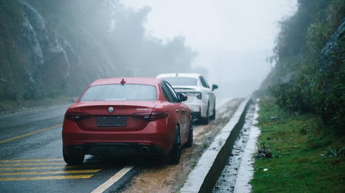 Cars parked on road on gloomy rainy day