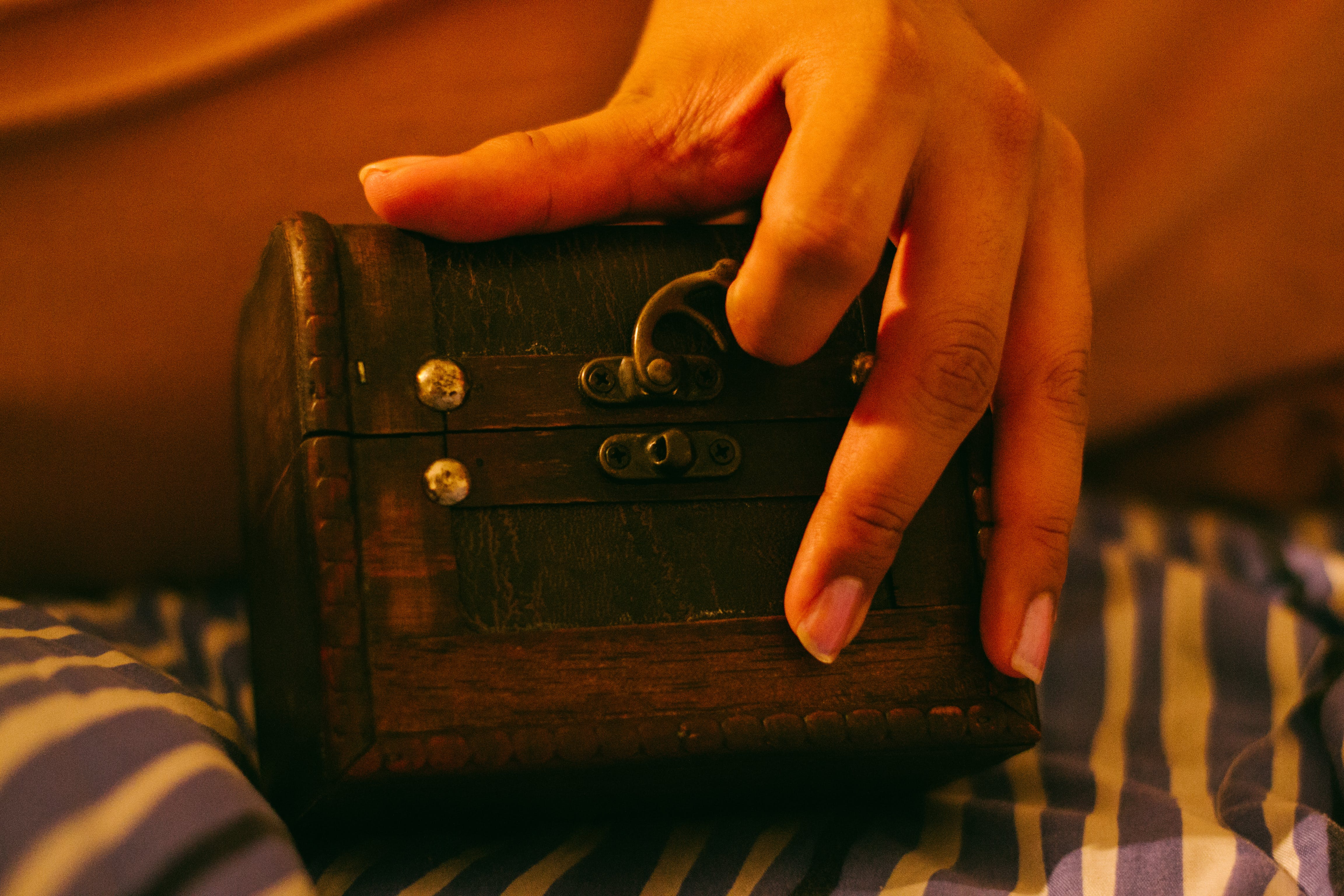 Person Holding Brown Wooden Chest
