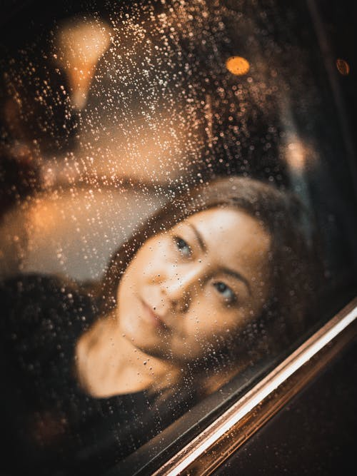 Pensive young female with long hair looking through glass window in rainy weather while sitting in car