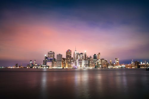 Magnificent remote view of illuminated skyscrapers on waterfront of modern megapolis at night