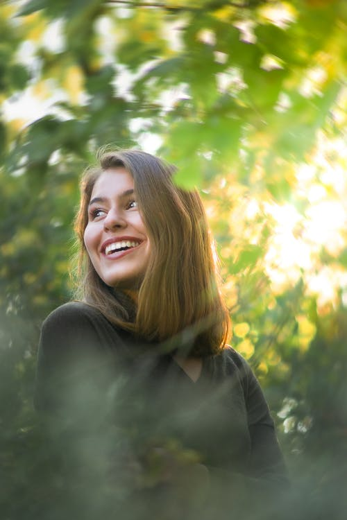 Smiling female standing in green park