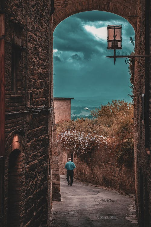 Back view full length male in casual clothes walking on narrow footpath along medieval stone buildings in ancient town on overcast cloudy weather