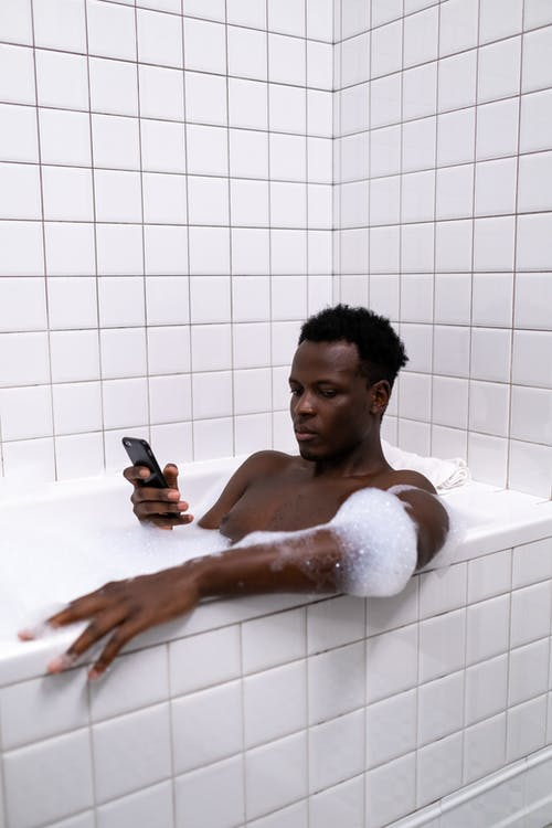 Man in Bathtub Holding Smartphone